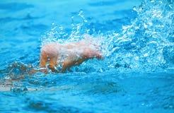 Плавать и пинать вода брызгают в бассейне Стоковые Изображения RF