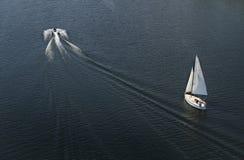 Плавать с белой лыжей ветрила и двигателя на голубой поверхности воды Стоковое Фото