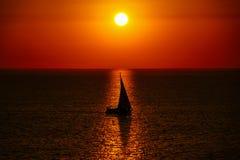 Плавать яхта в заходе солнца, тень парусника на предпосылке золотого захода солнца и отражение в стоковое фото rf