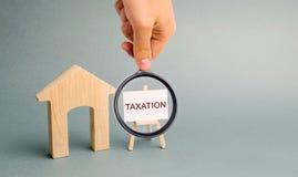 Плакат с обложением слова около миниатюрного деревянного дома Концепция бремени налогового обложения на свойстве Оплата налогов стоковая фотография
