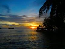 Пламенистый заход солнца зарева над красивым тропическим пляжем и океан мочат Другие цвета облаков и силуэта пальмы Стоковое Фото