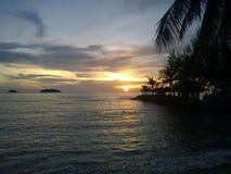 Пламенистый заход солнца зарева над красивым тропическим пляжем и океан мочат Другие цвета облаков и силуэта пальмы Стоковые Изображения RF