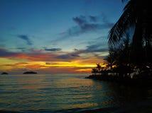 Пламенистый заход солнца зарева над красивым тропическим пляжем и океан мочат Другие цвета облаков и силуэта пальмы Стоковые Изображения