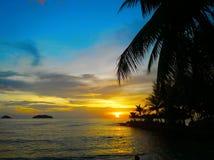 Пламенистый заход солнца зарева над красивым тропическим пляжем и океан мочат Другие цвета облаков и силуэта пальмы Стоковое фото RF