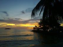 Пламенистый заход солнца зарева над красивым тропическим пляжем и океан мочат Другие цвета облаков и силуэта пальмы Стоковые Фотографии RF