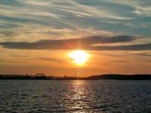 Пламенистый заход солнца зарева над морской водой Балтийского моря Другие цвета облаков и силуэта верфи в городе Гдыни, Польше Стоковые Изображения
