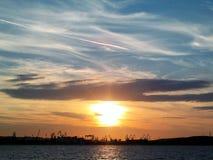 Пламенистый заход солнца зарева над морской водой Балтийского моря Другие цвета облаков и силуэта верфи в городе Гдыни, Польше Стоковое Изображение