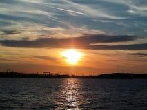 Пламенистый заход солнца зарева над морской водой Балтийского моря Другие цвета облаков и силуэта верфи в городе Гдыни, Польше Стоковое Изображение RF