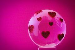 Планета влюбленности. Стеклянный глобус с красными сердцами. Стоковое Фото