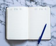 Плановик пустой страницы с голубой ручкой на мраморной предпосылке стоковое фото rf