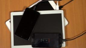 Планшеты и умные телефоны поручая на предпосылке деревянного стола сток-видео