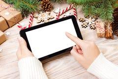 Планшет в руках девушки планшет с красными подарочной коробкой, конфетой рождества и елью разветвляет Открытый космос для текста  стоковая фотография