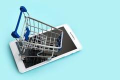 Планшет и малая тележка для ходить по магазинам на cyan предпосылке интернет принципиальной схемы 3d представляет покупку скопиру стоковые фотографии rf