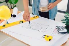 План архитектора работая и делая эскиз к архитектурноакустический чертежа на животиках Стоковое Изображение