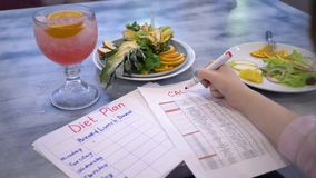 План диеты, женская рука с красной отметкой пишет калории слова на белой бумаге около красивой еды в плитах на таблице внутри акции видеоматериалы