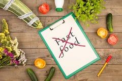 План диеты - сквош сердцевины, доска сзажимом для бумаги с текстом & x22; Отсутствие быстрого food& x22; , овощи и измеряя лента стоковые изображения rf
