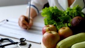 План диеты сочинительства женщины диетолога на таблице вполне фруктов и овощей сток-видео
