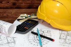 План дома, калькулятора, ручки, карандаша и шлема на деревянной таблице Стоковая Фотография