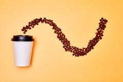 План кофейных зерен в волнистой линии на желтой предпосылке с белой ус стоковые фото