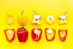План красных и желтых сладостных кусков болгарского перца на желтой картине взгляд сверху предпосылки Стоковое фото RF
