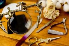 План на деревянной предпосылке в ретро стиле с ножницами в форме единорога, винтажной лупой с зажимами стоковые изображения rf