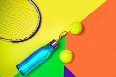 План с теннисными мячами, ракетка тенниса, бутылка воды на предпосылке конспекта различной пестротканой неоновой с местом для тек стоковое фото