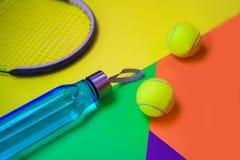 План с теннисными мячами, ракетка тенниса, бутылка воды на предпосылке конспекта различной пестротканой неоновой с местом для тек стоковые изображения