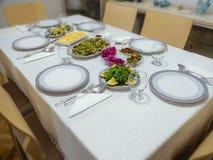 План таблицы подготовленный для обедающего в турецком доме семьи блюда плиты, вилк-ложки и салата на обеденном столе стоковая фотография rf