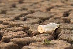 Пластиковая бутылка на земном загрязнении метафоры пластикового материала в воде и природе стоковая фотография rf
