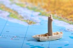 Пластиковая игрушка - корабль или шлюпка плавая на карту или атлас с морем, океаном и землей - соответствующая как реклама на пер стоковая фотография