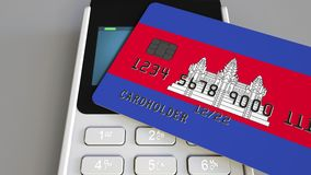 Пластиковая карта банка отличая флагом Камбоджи и терминала оплаты POS Камбоджийская банковская система или розничное родственное видеоматериал
