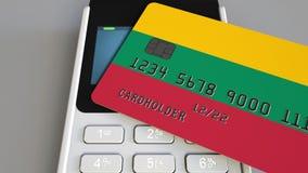 Пластиковая карта банка отличая флагом Литвы и терминала оплаты POS Литовская банковская система или розничное родственное 3D сток-видео