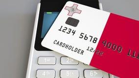 Пластиковая карта банка отличая флагом Мальты и терминала оплаты POS Мальтийская банковская система или розничное родственное 3D акции видеоматериалы