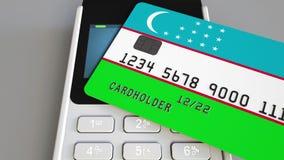 Пластиковая карта банка отличая флагом Узбекистана и терминала оплаты POS Узбекская банковская система или розничное родственное  акции видеоматериалы