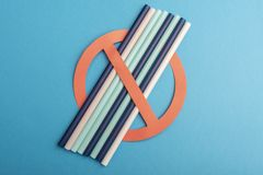 Пластиковые соломы используемые для питьевой воды или лимонадов концепция протеста на голубой предпосылке Отсутствие пластмассы стоковые изображения rf