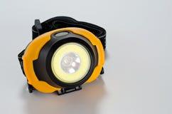 Пластиковый желтый цвет черноты электрофонаря головы СИД на белой предпосылке стоковое изображение