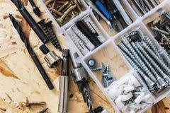 Пластиковый прозрачный организатор с винтами, шпонками, сверлами, битами на предпосылке OSB стоковые изображения
