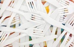 Пластичные белые вилки и ножи на скатерти Стоковое Изображение