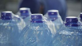 Пластичные бутылки с водой в упаковывая стойке в мастерской завода крытой акции видеоматериалы