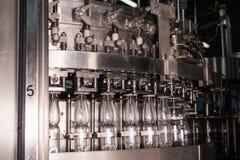 Пластичные бутылки с водой на индустрии разливая по бутылкам машины транспортера и воды Стоковое Изображение RF
