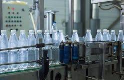 Пластичные бутылки с водой на индустрии разливая по бутылкам машины транспортера и воды Стоковая Фотография