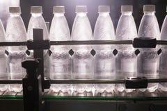 Пластичные бутылки с водой на индустрии разливая по бутылкам машины транспортера и воды Стоковые Фото