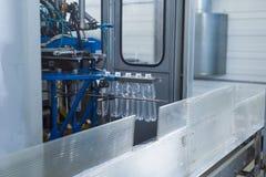 Пластичные бутылки с водой на индустрии разливая по бутылкам машины транспортера и воды Стоковое Изображение