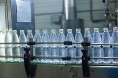 Пластичные бутылки с водой на индустрии разливая по бутылкам машины транспортера и воды Стоковые Изображения