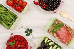 Пластичные контейнеры приготовления уроков еды с зелеными горохами, клубниками, blac стоковое фото rf