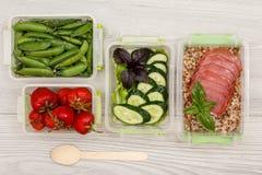Пластичные контейнеры приготовления уроков еды с свежими клубниками, зелеными горохами стоковые фото
