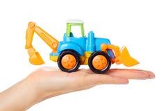 Пластичный трактор игрушки в руке изолированной на белой предпосылке Стоковые Изображения RF