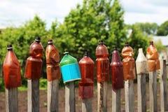12 пластичных бутылок одн-галлона воды и моча чонсервной банкы на том основании в саде общины Стоковое Изображение