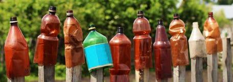 12 пластичных бутылок одн-галлона воды и моча чонсервной банкы на том основании в саде общины Стоковое фото RF