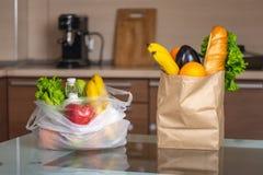 Пластмасса и бумажные мешки с едой на кухонном столе Выбор пользы экол стоковые изображения